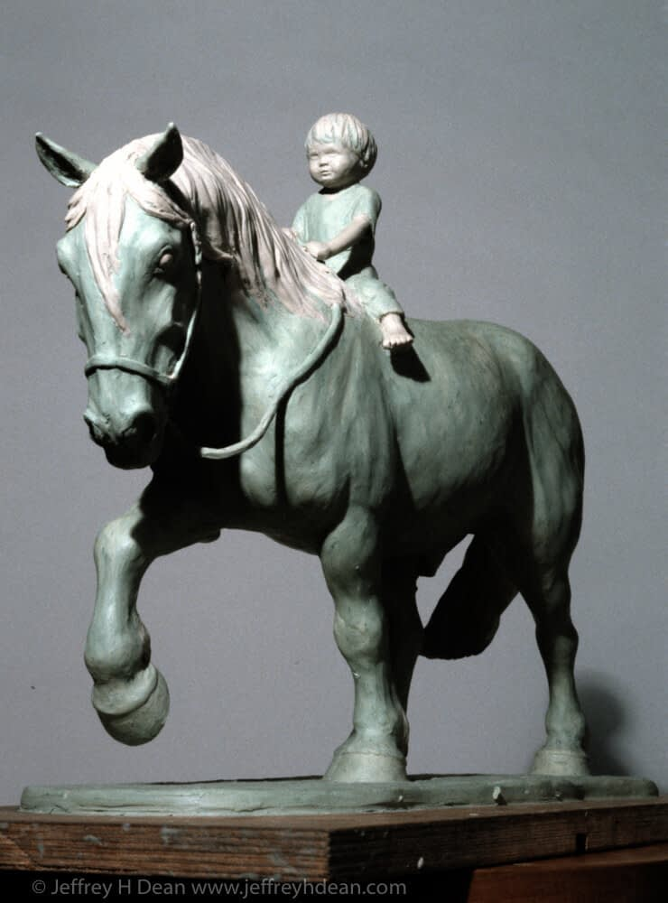 Clay model of a young boy riding a draft horse.