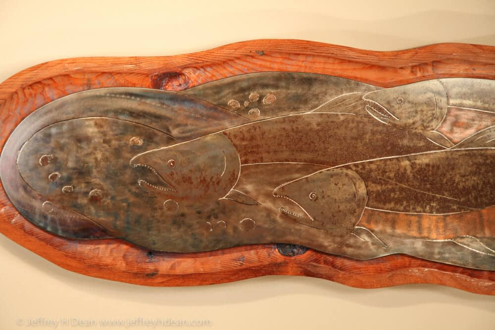 Three salmon rest in the shallow headwaters of a northern stream bed. Engraved steel wall relief.