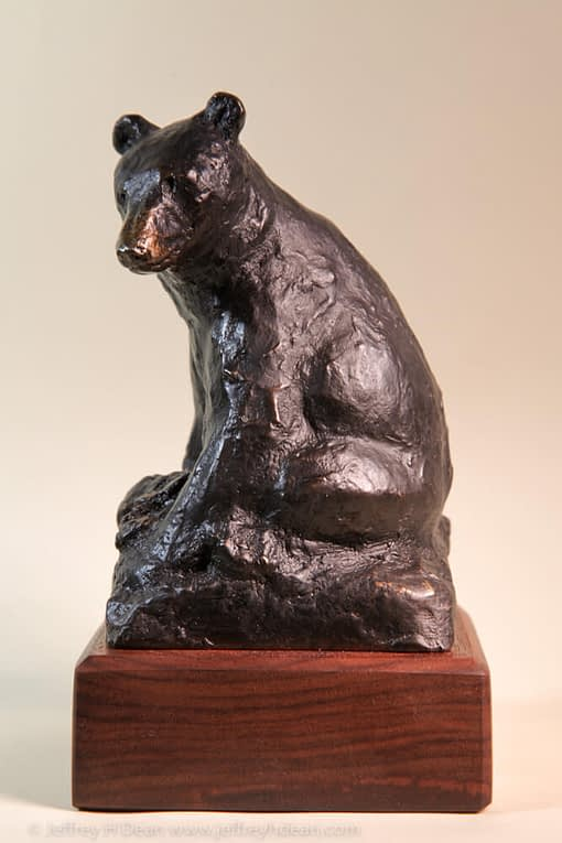 Bronze sketch of seated black bear.