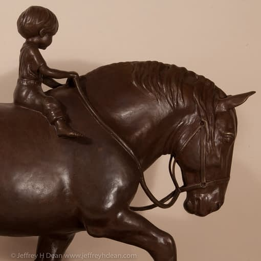 Bronze sculpture of a young boy riding a draft horse.