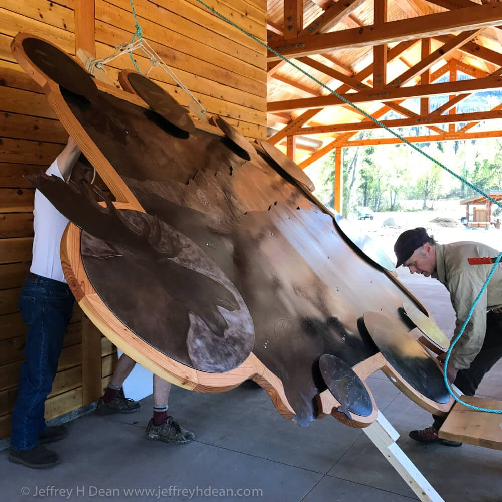 Hoisting the steel wall art into a vertical position against the Kesugi Ken Interpretive Center wall.