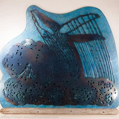 A humpback whale breaches in front of Mt. Augustine sunset in this wood and metal wall art