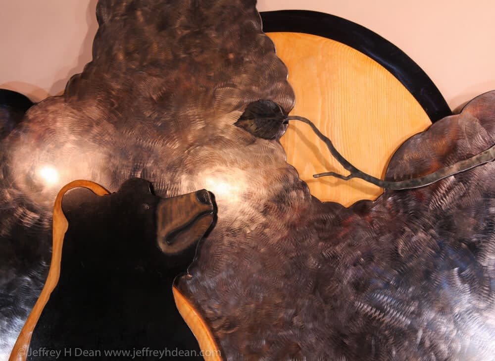 Layered steel and wood wall art of a fishing black bear, a salmon, a raven in a birch tree.