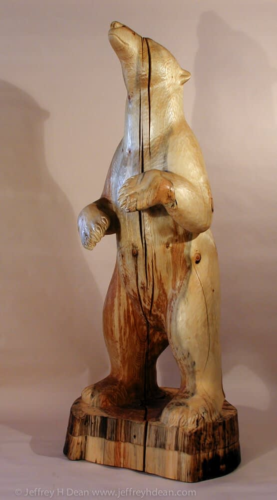 White spruce carving of polar bear sniffing at the wind.