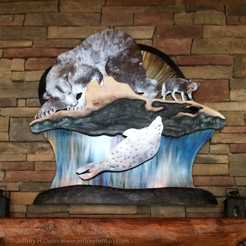 A lone polar bear and arctic fox watch silently as a seal rises to it's breathing hole in this layered metal and wood wall art..