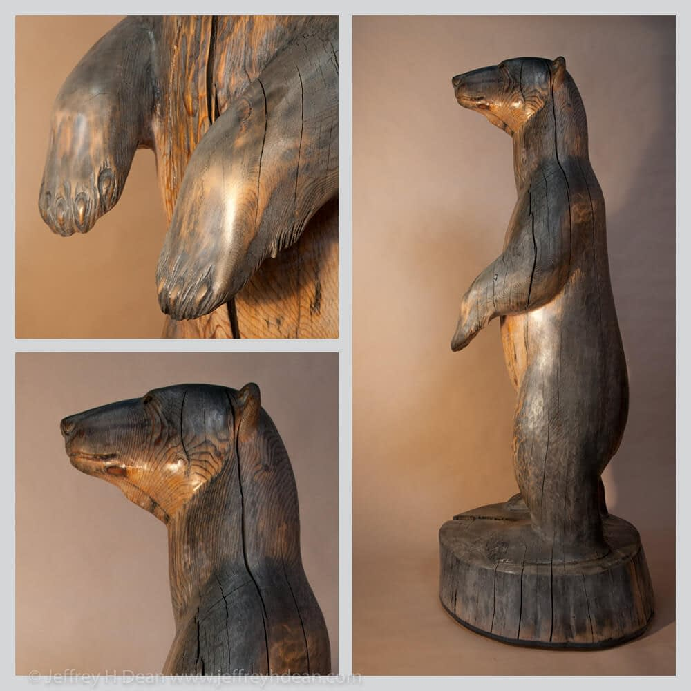 6.5' tall white spruce carving of polar bear in the rays of the first arctic sun.