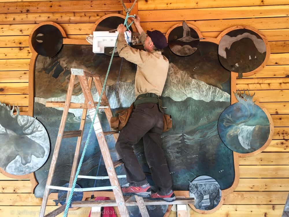 Jeff removing the hoisting line in preparation for fasting wall art to the wall.