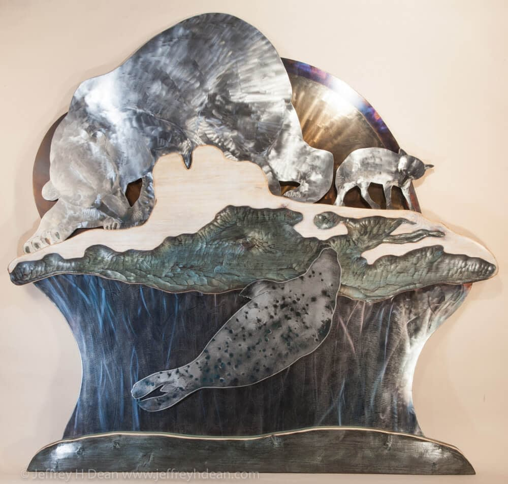 A lone polar bear and arctic fox watch silently as a seal rises to it's breathing hole in this layered metal and wood wall art.