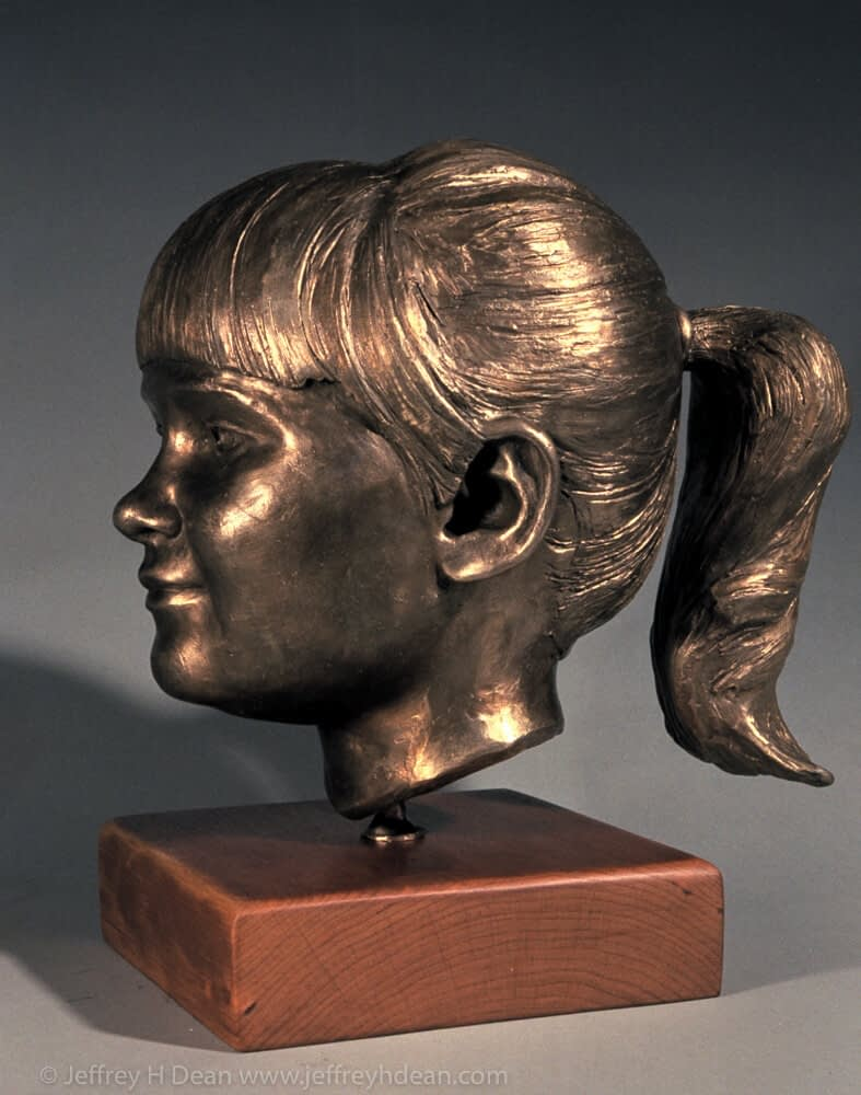 Bronze portrait of a young girl with pony tail.