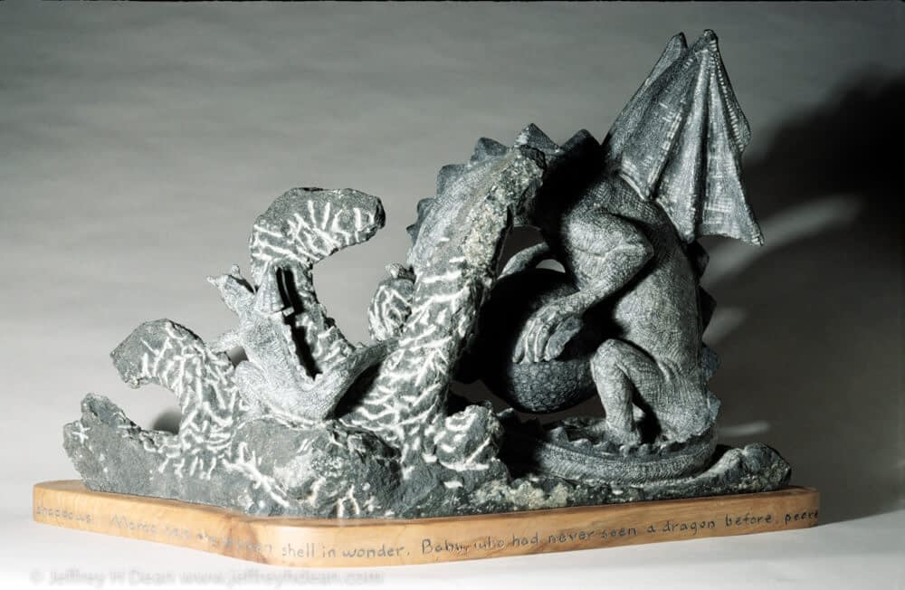 Stone carving of mother and baby dragon with the beginning of a story around the base.