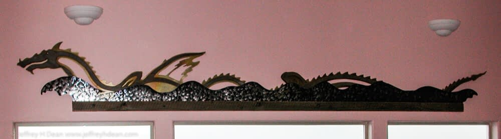 Wall relief of sea dragon frolicking in the waves. Weathered fir, stainless steel and brass.