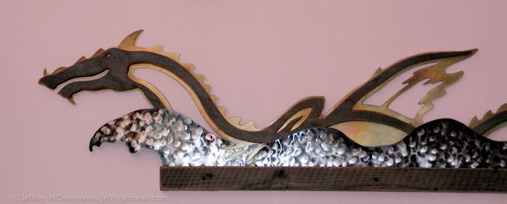 Wall relief of sea dragon frolicking in the waves. Weathered fir, stainless steel and brass wood and metal wall art