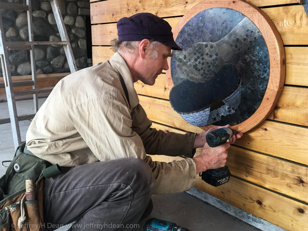 Jeffrey H. Dean installing bearing picking picture as part of Through Your Spotting Scope percent for art commission at Denali State Park.