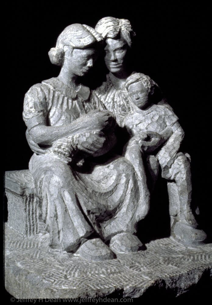 Stone carving of family with newborn child