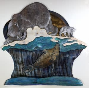 A lone polar bear and arctic fox watch silently as a seal rises to its breathing hole in this layered metal and wood wall art.