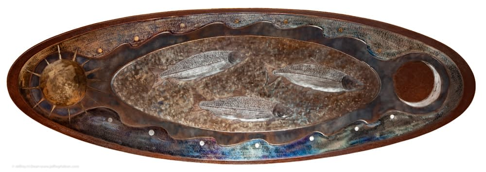 "A 62"" work of metal wall art with three silver salmon swimming between the tides, the sun and moon."