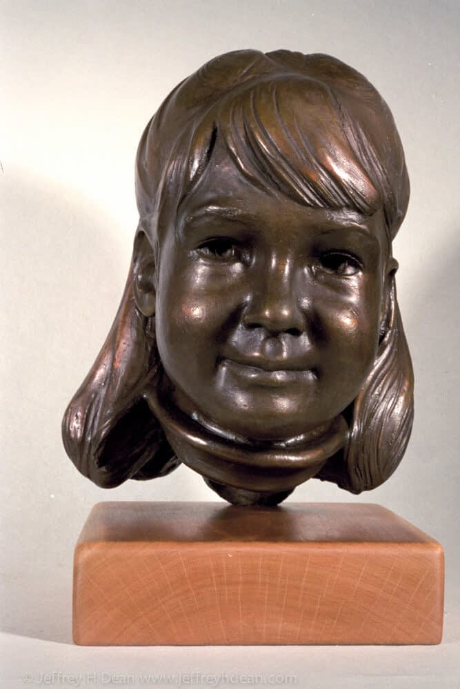 A bronze portrait sculpture of a young girl.