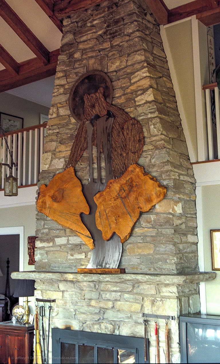 Large wood and metal wall art of a fishing bear with the sun shining from behind on rock chimney wall.