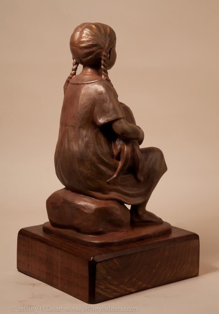 Bronze sculpture of a young girl holding her rooster.