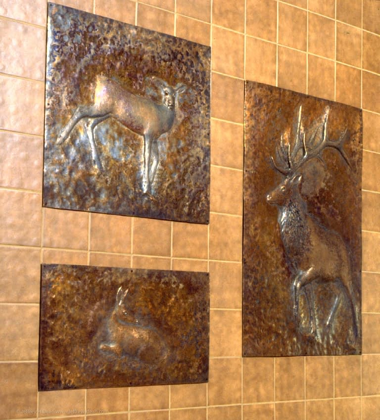 Hammered copper panels of an elk family used as a heat shield for a wood stove.