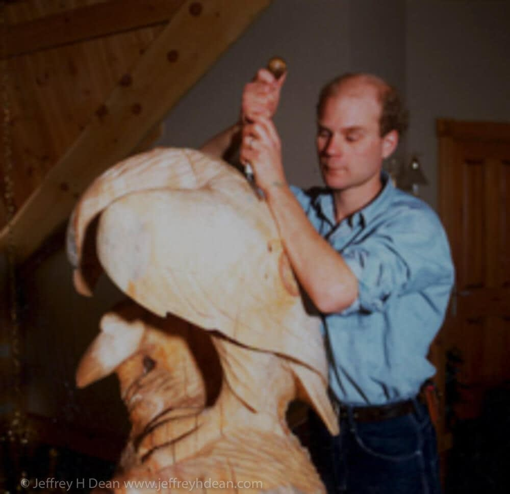 """Jeff Dean carving a golden eagle in the top end of a 24"""" octagon house post."""