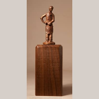 Bronze miniature sculpture of a woodcarver holdiing his mallet and chisel.