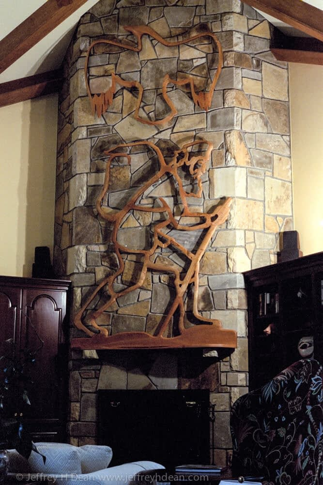 Fireplace mantle and pierced cherry relief of hiking mountain man and raven.