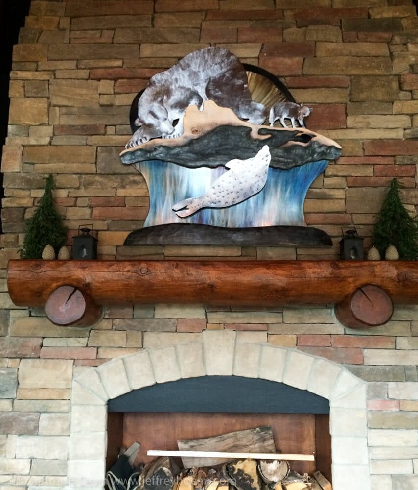 A lone polar bear and arctic fox watch silently as a seal rises to it's breathing hole in this layered steel and wood relief.